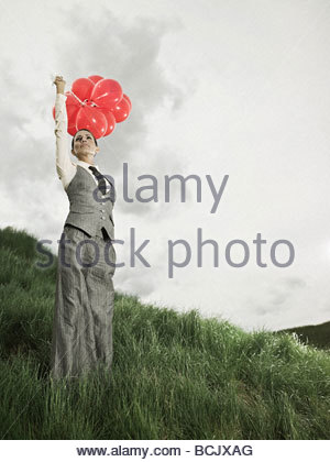 Businesswoman outdoors with balloons - Stock Photo