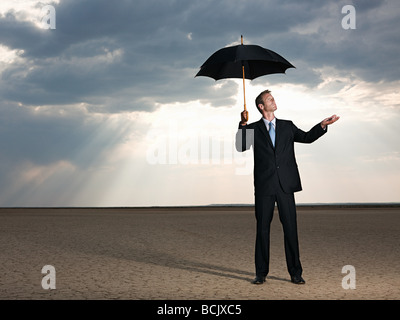 Businessman in the desert with an umbrella - Stock Photo