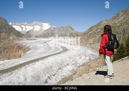 Hiker near aletsch glacier in switzerland - Stock Photo
