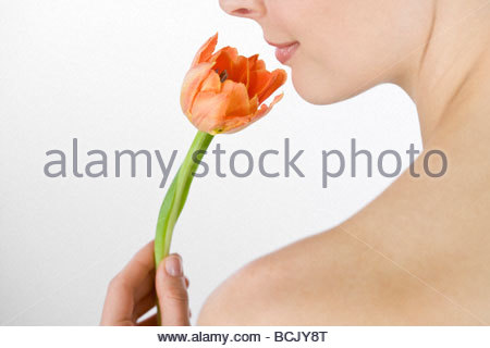 A young woman holding an orange tulip, side view - Stock Photo