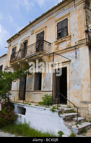 Exterior of houses left abandoned and derelict after 1953 earthquake in village of Assos on  Greek island of Kefalonia - Stock Photo