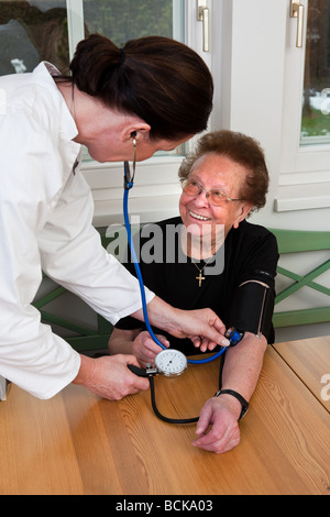 A physician measures the blood pressure of a patient - Stock Photo