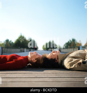 Young man and woman lying on ground head to head - Stock Photo