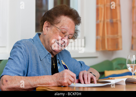 Old woman writes a letter - Stock Photo