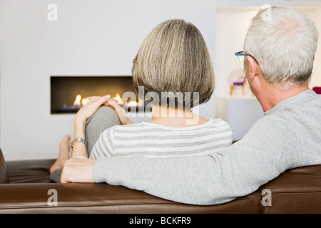 Mature couple sat next to the fire - Stock Photo