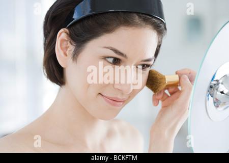 Young woman applying make up - Stock Photo