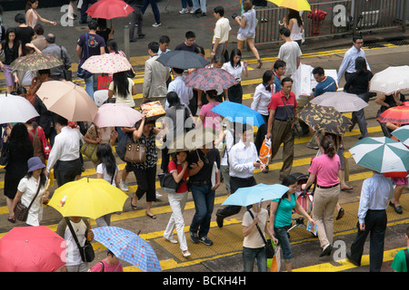 China Hong Kong pedestrians crossing road in the rain in Central district - Stock Photo