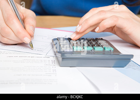 Person with calculator and forms Stock Photo