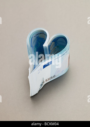 Twenty euro notes in heart shape - Stock Photo