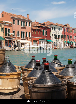 Venice - Murano island delivery of restaurant house wine in demijohn bottles by barge - Stock Photo