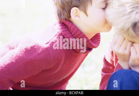 Child kissing second child on cheek - Stock Photo