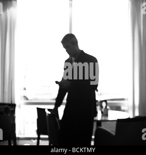 Man looking at phone, silhouette - Stock Photo