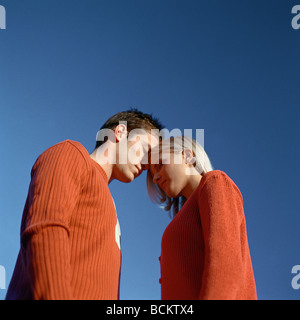 Man and woman standing head to head, low angle view - Stock Photo