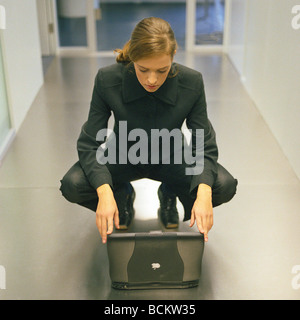 Woman crouching down in front of laptop - Stock Photo