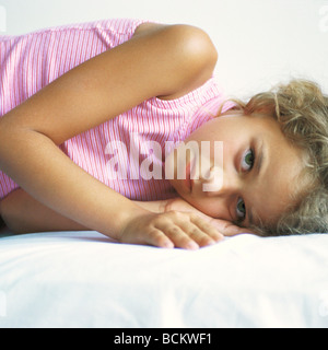Girl lying on bed, looking into camera - Stock Photo