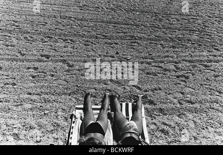 Two women sunbathing, lower section, high angle view, b&w - Stock Photo