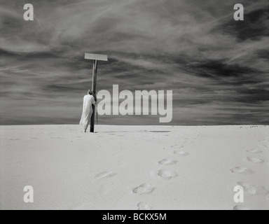 Woman standing next to pole on sand, b&w - Stock Photo