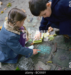 Boy and girl coloring on ground with chalk - Stock Photo