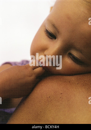 Child with fingers in mouth leaning against mother's bare shoulder - Stock Photo