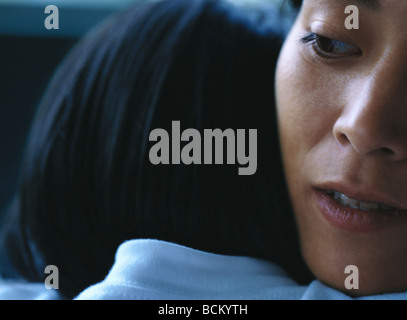 Child resting head on mother's shoulder - Stock Photo