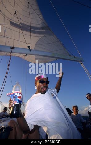 A black man with pirate bandanna dancing at evening on a catamaran ship Caribbean sea - Dominican Republic Island - Stock Photo