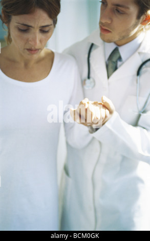 Doctor holding female patient's hand - Stock Photo