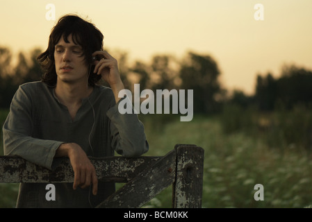 Teenage boy leaning against wooden gate, listening to headphones, waist up - Stock Photo