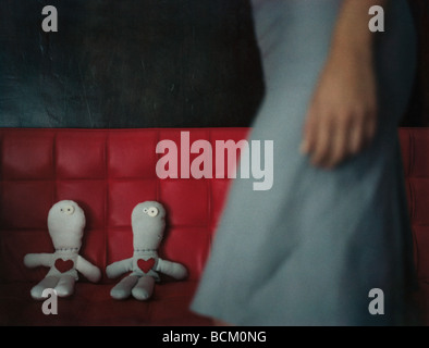 Woman walking by two rag dolls on red sofa, mid section - Stock Photo