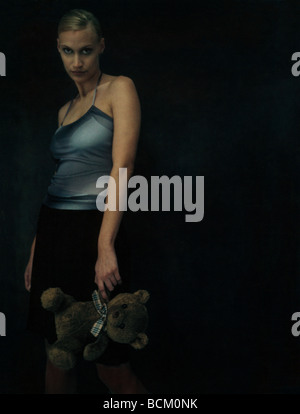 Woman standing in dark, holding teddy bear, looking at camera - Stock Photo