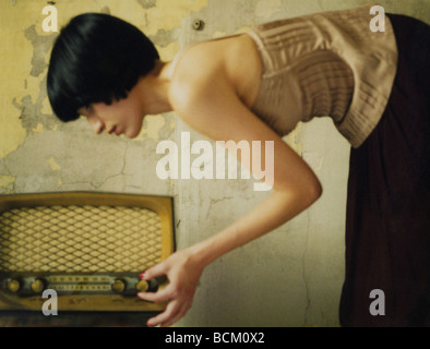 Woman bending over, turning dial on old fashioned radio - Stock Photo