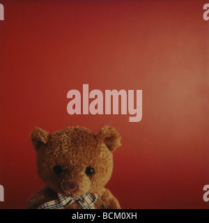 Teddy bear against red background, cropped view - Stock Photo