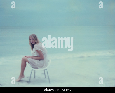 Young female sitting in chair on beach, looking at camera, full length - Stock Photo