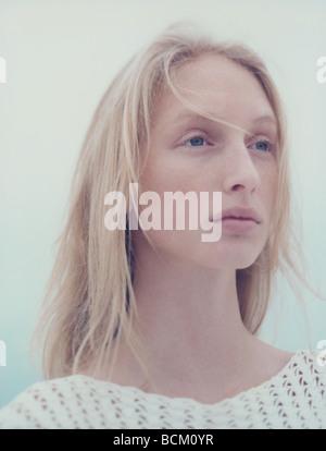 Teenage girl with windblown hair, looking away, portrait - Stock Photo