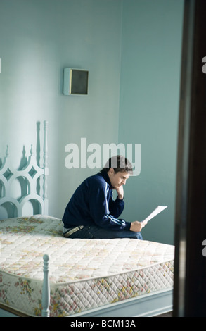 Young man sitting on edge of bed, reading document - Stock Photo