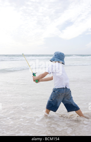 Boy standing in shallow water, using fishing pole - Stock Photo
