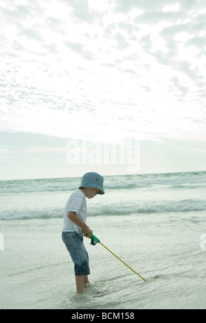 Boy standing in shallow water, holding fishing pole - Stock Photo