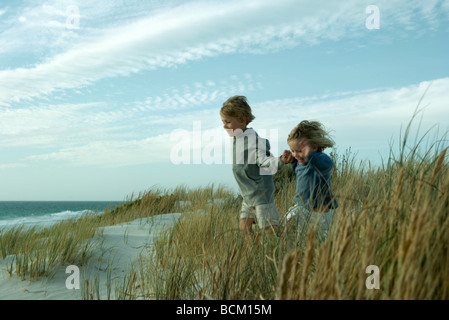 Boy and girl running through dune grass, holding hands - Stock Photo