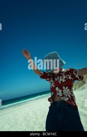 Boy on beach with arms raised, wearing beach clothes, close-up - Stock Photo
