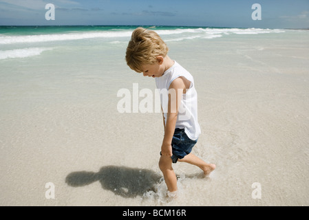 Boy running in surf at beach, high angle view, full length - Stock Photo