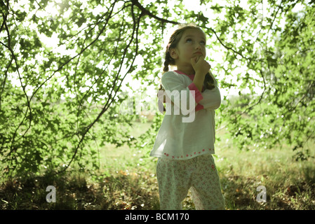 Girl standing under branches, looking up - Stock Photo