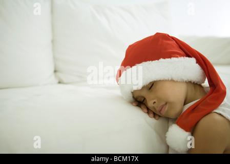 Child sleeping with head on sofa, wearing santa hat, close-up - Stock Photo