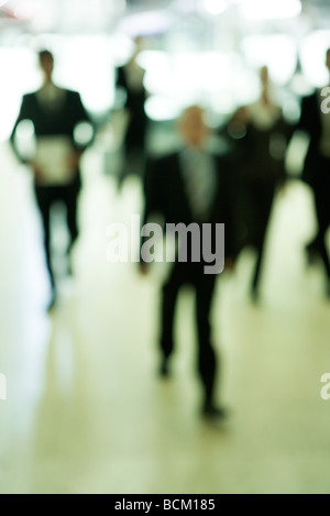Business people walking through lobby, front view, defocused - Stock Photo
