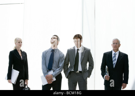 Business people standing in various poses, three quarter length, front view - Stock Photo