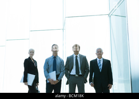 Business team smiling at camera, front view, three quarter length - Stock Photo