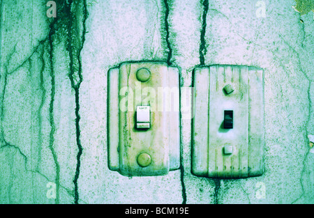 Lightswitches on dirty wall, green toned - Stock Photo