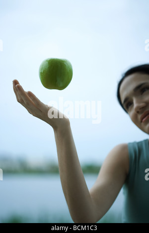 Apple floating in air above woman's hand, cropped view