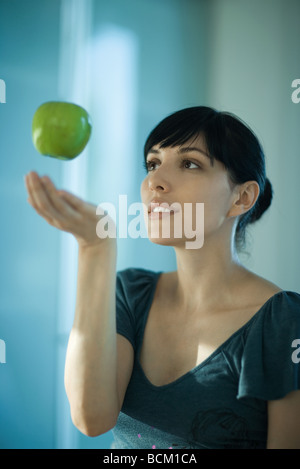 Apple floating in air above woman's hand