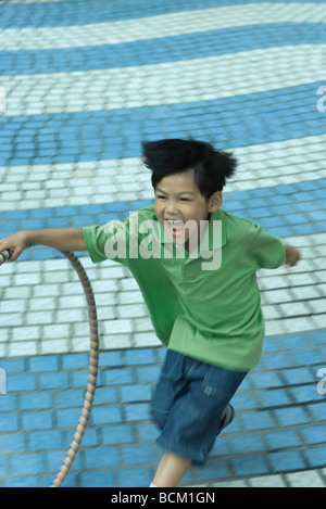 Boy running with plastic hoop and yelling, blurred motion - Stock Photo
