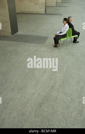 Businesswoman and businessman sitting back to back, high angle view, full length - Stock Photo