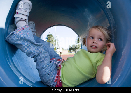 Girl lying in playground tunnel with legs up, looking away, close-up - Stock Photo